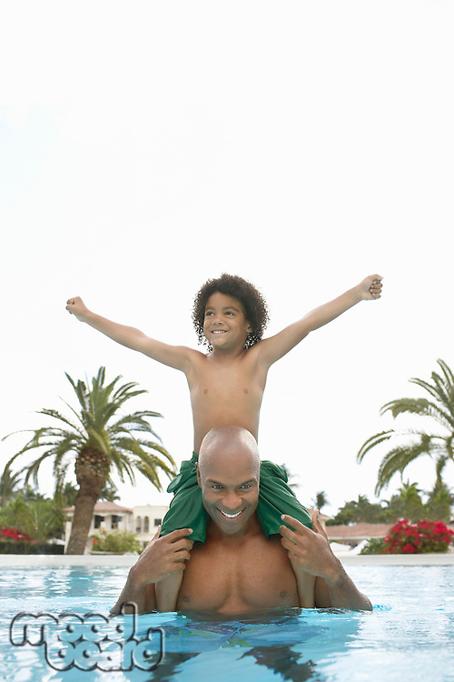 Father carrying son on shoulders son (5-6 years) standing in swimming pool
