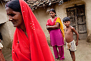 """(L-R) Kelaji Adivasi (45), Dharma (18, soon to be married), and Akanksha (8) stand in their house in a tribal hamlet. Kelaji's husband, Tribhuvan, a farm labourer, says that """"it was a mistake to have so many children. Food is difficult for us."""" Kelaji and Tribhuvan have a total of 6 children and live in poverty in Baul ka Dhera hamlet, Mugari Village, Allahabad, Uttar Pradesh, India. Allahabad, a poorer district of the state of Uttar Pradesh, is the most populated district of the most populous state of India. While Ghaziabad, located close to India's capital city, Delhi, has a population of 4,661,452 with a sex ratio of 878 girls against every 1000 boys, and a high literary percentage of 85%, Allahabad, has a population of 5,959,798 and a sex ratio of 902 girls against every 1000 boys and a literacy rate of 74.41%. Photo by Suzanne Lee / Panos London"""