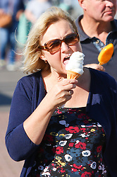© Licensed to London News Pictures. 27/09/2015. Brighton, UK. People relax in the sun while having an ice cream on Brighton Beach. Today September 27th 2015. Photo credit : Hugo Michiels/LNP