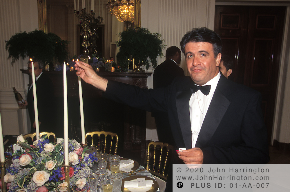 AS GUESTS ARE GREETED BY THE PRESIDENT, BUTLERS IN THE EAST ROOM LIGHT THE CANDLES ON EACH TABLE FOR THE STATE DINNER