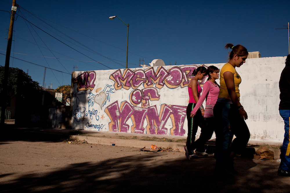 A group of young women walk by a mural commemorating a massacre that left 13 dead and over a dozen wounded in Ciudad Juarez, Mexico. Most of the victims were between the ages of 14 and 20 years old and were attending a birthday party.