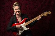 Portrait of Rachel M. in studio strumming on a red Fender guitar