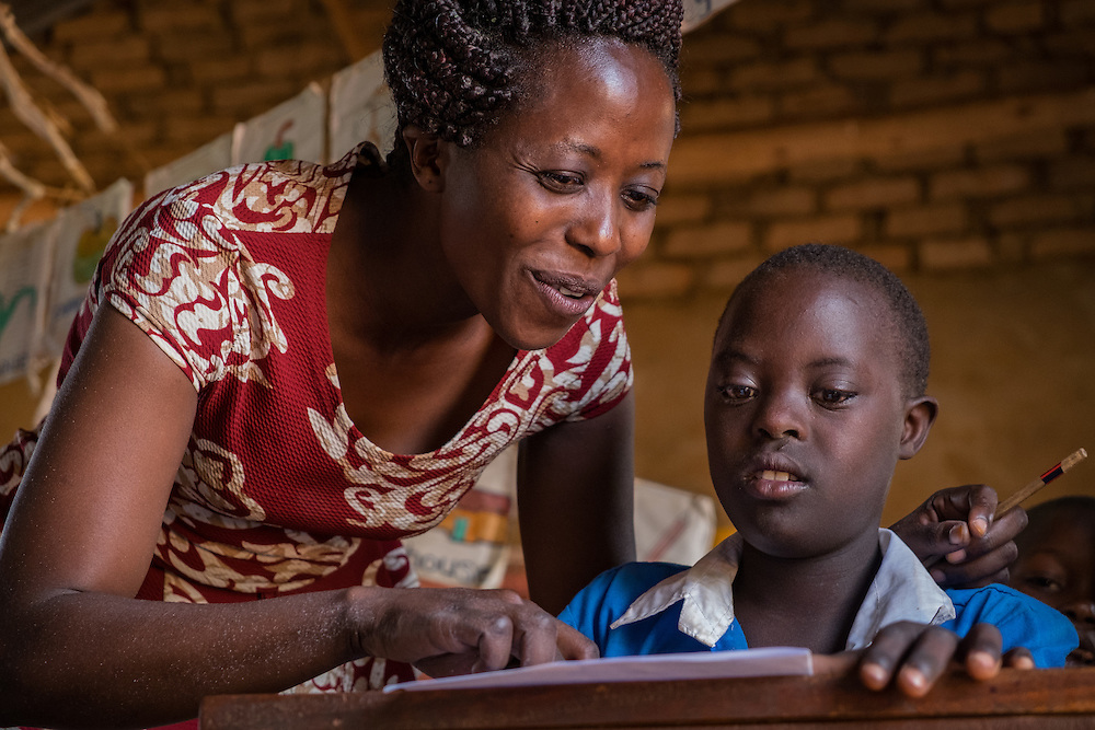 CAPTION: Teacher Margaret Nabwami helps Junior, a student with both a hearing impairment and a learning disability, during class. Ms Nabwami is a SignHealth Uganda 'focus teacher' at Butenga-Kibanda Primary School. She has received special training in how to work with children who have hearing impairments, which she puts into effect in her own classroom and also teaches to other staff at the school. LOCATION: Butenga-Kibanda Primary School, Butenga Village, near Masaka City, Bukomansimbi District, Central Region, Uganda. INDIVIDUAL(S) PHOTOGRAPHED: Left: Margaret Nabwami; right: Junior Steven Ssengodze.