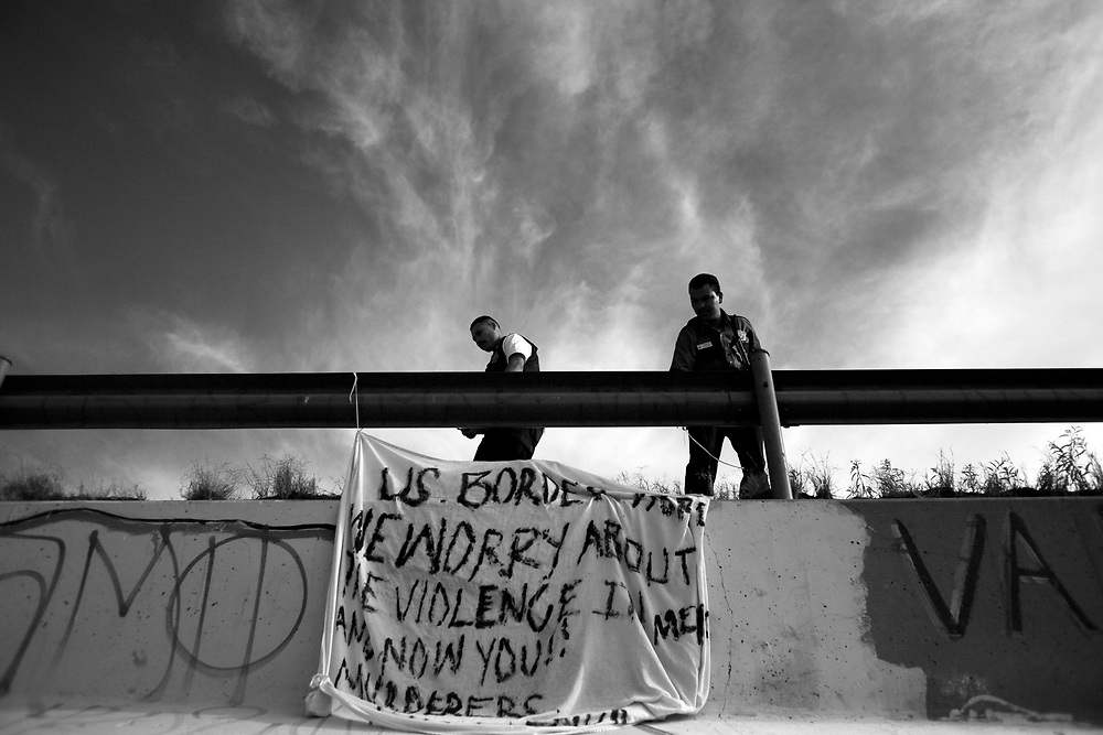 "Mexican Municipal Police from Juarez remove a banner that says ""US BORDER PATROL WE WORRY ABOUT VIOLENCE IN MEXICO AND NOW YOU!! MURDERERS.VIVA MEXICO."" The banner was a protest against the killing of 15-year-old Sergio Adrian Hernandez Guereca, who was killed yesterday by a Border Patrol agent. The banner was hung on the Mexican side between the ""Puente Juarez"" bridge and the ""Puente Negro"" bridge."