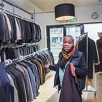 Nederland, Amsterdam, 3 februari 2017.<br /> Mevrouw Hoogvliet is bewoonster van de z.g. wuifwoning in de Poeldijkstraat.<br /> De Poeldijkstraat 10 biedt onderdak aan ruim 180 bewoners van De Rijswijk, De Veste en het Passantenverblijf en is ook kantoor is voor het Mobiel Team. Het pand  telt twaalf verdiepingen en biedt dus het mooiste uitzicht over de stad. <br /> Er wonen 40 bewoners verdeeld over de vier verdiepingen. De tweede verdieping is aangepast voor bewoners met een bovengemiddelde fysieke zorgbehoefte. Op die kamers is het bijvoorbeeld mogelijk om een alarm te krijgen en is er voor de bewoners een specifiek zorgplan. Het pand is rolstoelvriendelijk. Alle medicatie is bij de begeleiding in beheer en er zijn vier uitdeelmomenten per dag.<br /> <br /> Er wonen acht bewoners in een zelfstandige flat op drie minuten lopen van het pand aan de Poeldijkstraat. Zij hebben ook een mentorkoppel die hen begeleidt vanuit de Veste. Bewoners van de flat hebben hun medicatie in eigen beheer.<br /> Op de foto: Mevrouw Hoogvliet helpt ook mee met kleiding uitzoeken en sorteren uitzoeken in de inpandige tweedehands kledingzaak.<br /> <br /> Foto: Jean-Pierre Jans