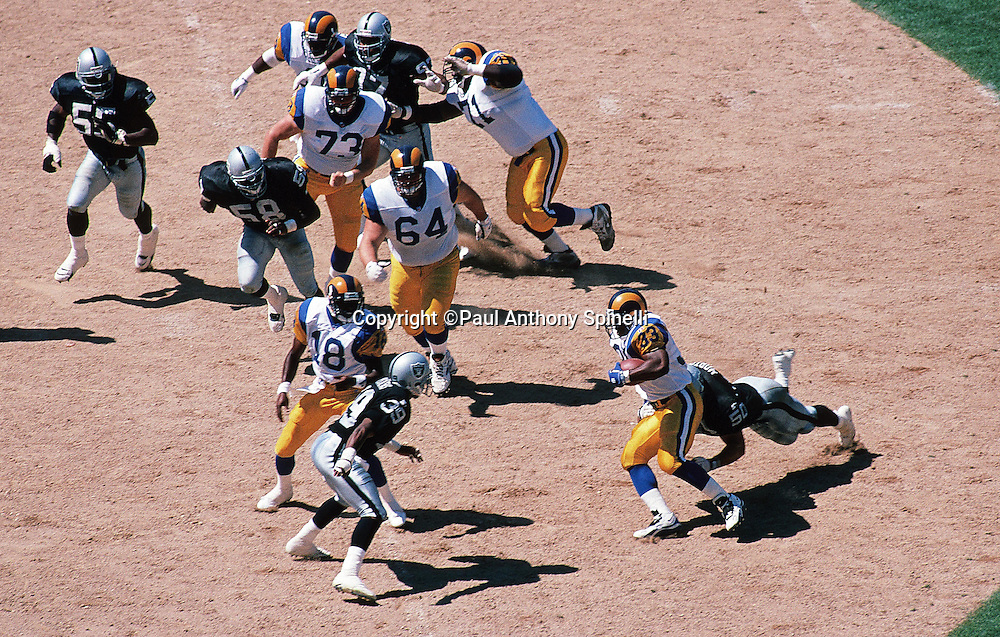 An unidentified St. Louis Rams running back (33) runs the ball in this overhead general view photo taken during the NFL preseason football game against the Oakland Raiders on Aug. 12, 1995 in Oakland, Calif. The Raiders won the game 27-22. (©Paul Anthony Spinelli)