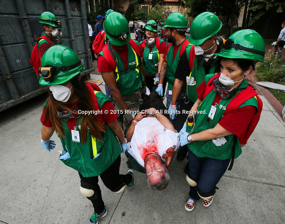 Rescuers carry a mock victim on a lounge chair during the annual Great California ShakeOut earthquake drill at Southern California University (USC) in Los Angeles on October 15, 2015. About 10.4 million Californian's registered to take part in the annual drill that asks participants to 'drop'' to the ground, take 'cover'' under a desk, table or other sturdy surface, and 'hold on'' for 60 seconds, as if a major earthquake were occurring.(Photo by Ringo Chiu/PHOTOFORMULA.com)