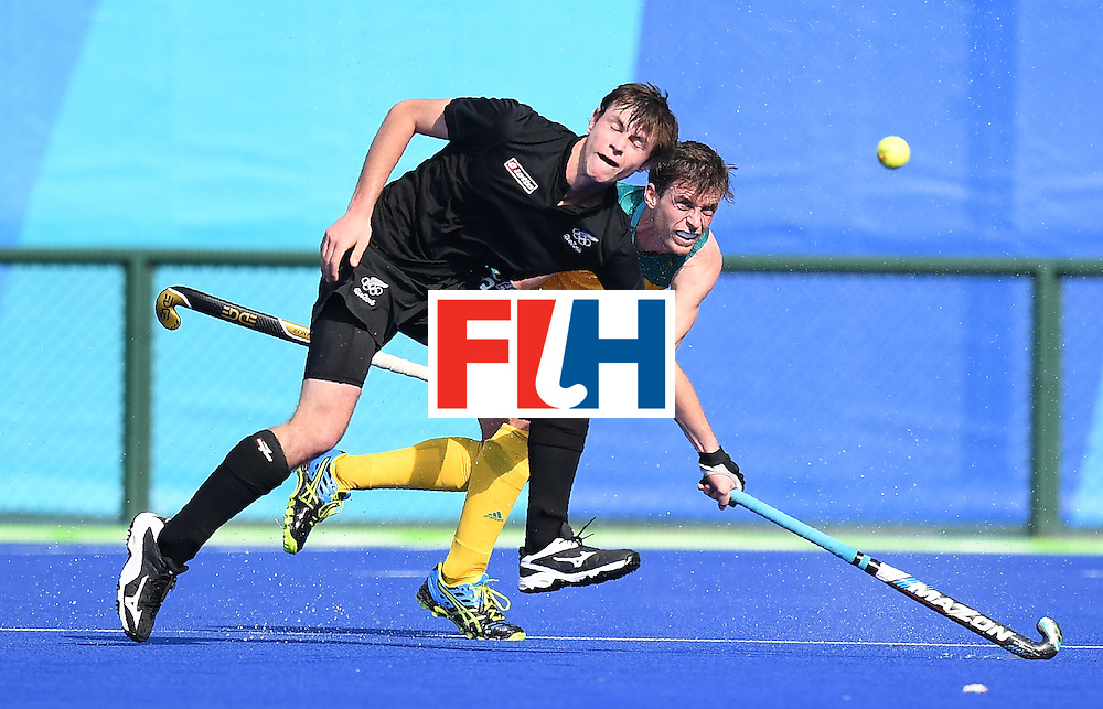 Australia's Fergus Kavanagh hits the ball as New Zealand's Nick Wilson looks on during the men's field hockey Australia vs New Zealand match of the Rio 2016 Olympics Games at the Olympic Hockey Centre in Rio de Janeiro on August, 6 2016. / AFP / MANAN VATSYAYANA        (Photo credit should read MANAN VATSYAYANA/AFP/Getty Images)