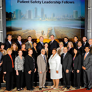 A group portrait during a medical conference shows everyone looking their best in front of a title slide on the projector screen. Event photography by Dallas corporate photographer William Morton of Morton Visuals.