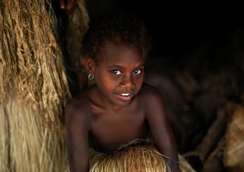 Vanuatu, Tafea Province, Tanna Island, girl hiding in the vegetal skirt of her mother
