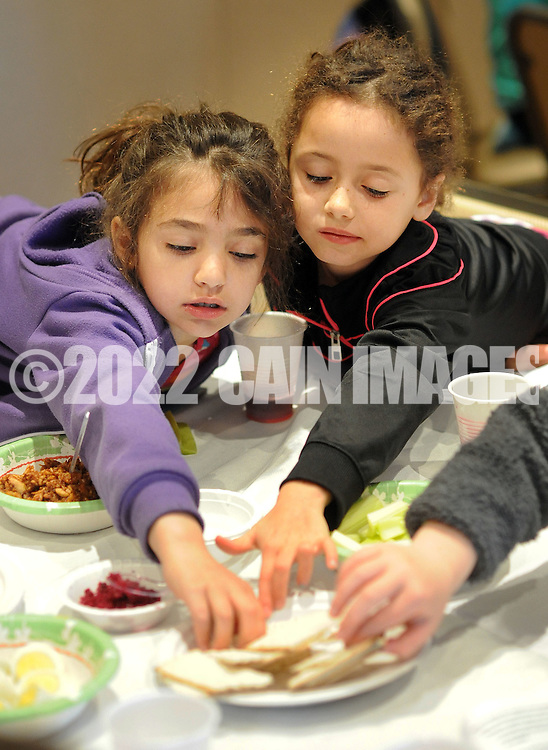 From left, Jade Kotzker and Ella Roskein reach for some matzo as they participate in seder dinner as part of Passover Palozza in preparation for the holiday Sunday April 17, 2016 at Congregation Beth El in Lower Makefield, Pennsylvania. (Photo by William Thomas Cain)
