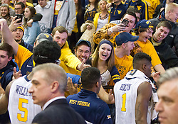 West Virginia fans celebrate with players after beating the Texas Longhorns at the WVU Coliseum.