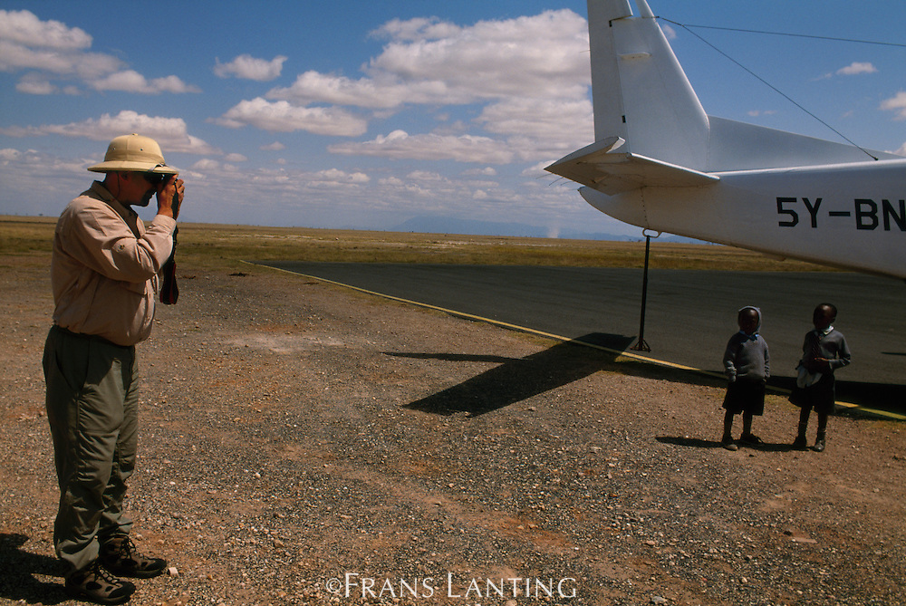Tourist with children on airstrip, Amboseli National Park, Kenya