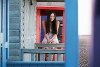 Woman sitting on balustrade of beach house portrait