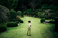 A Japanese woman in a green kimono in the middle of a green garden in Kyushu, Japan.