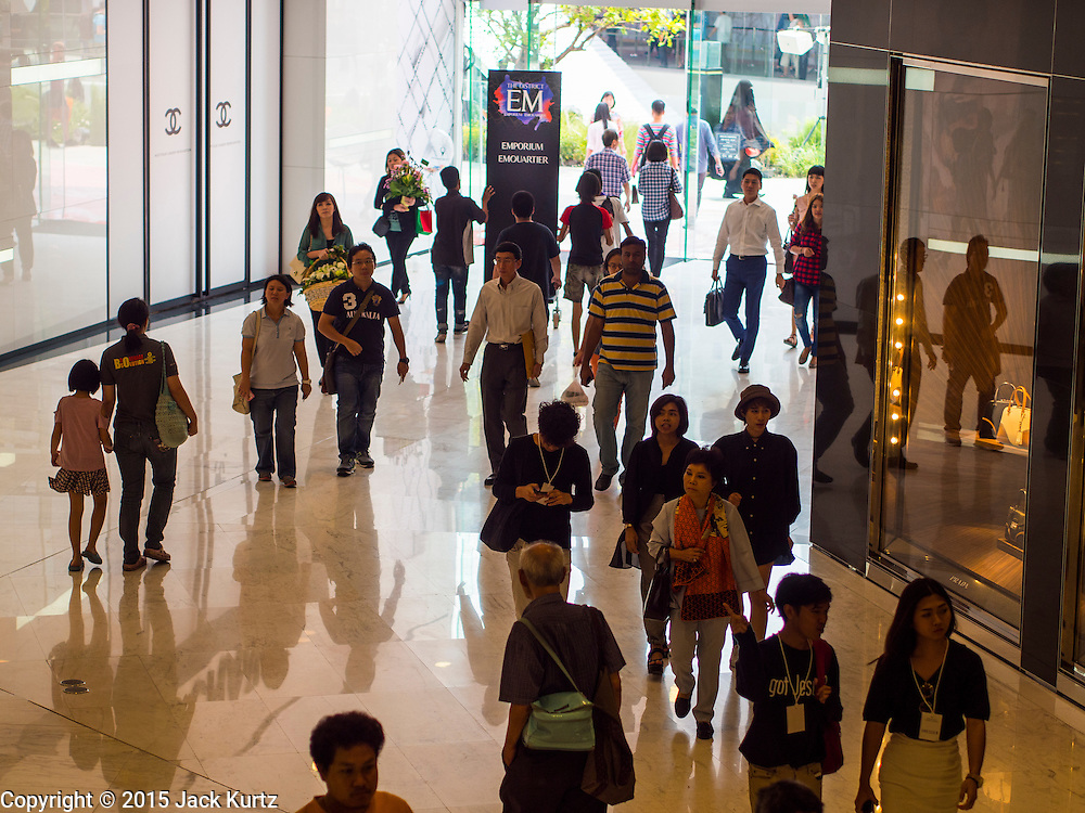 """27 MARCH 2015 - BANGKOK, THAILAND: Shoppers walk into """"EmQuartier,"""" a new shopping mall in Bangkok.  """"EmQuartier"""" is across Sukhumvit Rd from Emporium. Both malls have the same corporate owner, The Mall Group, which reportedly spent 20Billion Thai Baht (about $600 million US) on the new mall and renovating the existing Emporium. EmQuartier and Emporium have about 450,000 square meters of retail, several hotels, numerous restaurants, movie theaters and the largest man made waterfall in Southeast Asia. EmQuartier celebrated its grand opening Friday, March 27.   PHOTO BY JACK KURTZ"""