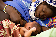 Bamakan Souko, 27, breast feeds her newborn girl while lying on a bed at the Kita reference health center in the town of Kita, Mali on Friday August 27, 2010.