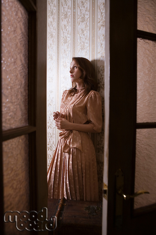 Young woman through glass panelled doors of Russian apartment