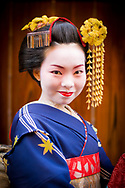 A Geisha poses for pictures in a small Kyoto, Japan, alleyway.