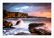 The sandstone cliffs north of Coogee Beach, Sydney catching the early morning autumn sunshine. View from Coogee towards Gordon's Bay and Clovelly. [Coogee, NSW, Australia]<br />