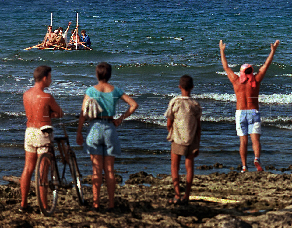 8/1994-Al Diaz/Miami Herald--In 1994 Cuban balseros turned the tiny fishing village of Cojimar into a major point of embarkation for thousands seeking a better life. Here, Cuban rafters depart the coast of Cojimar as spectators watch from the rocky beach.
