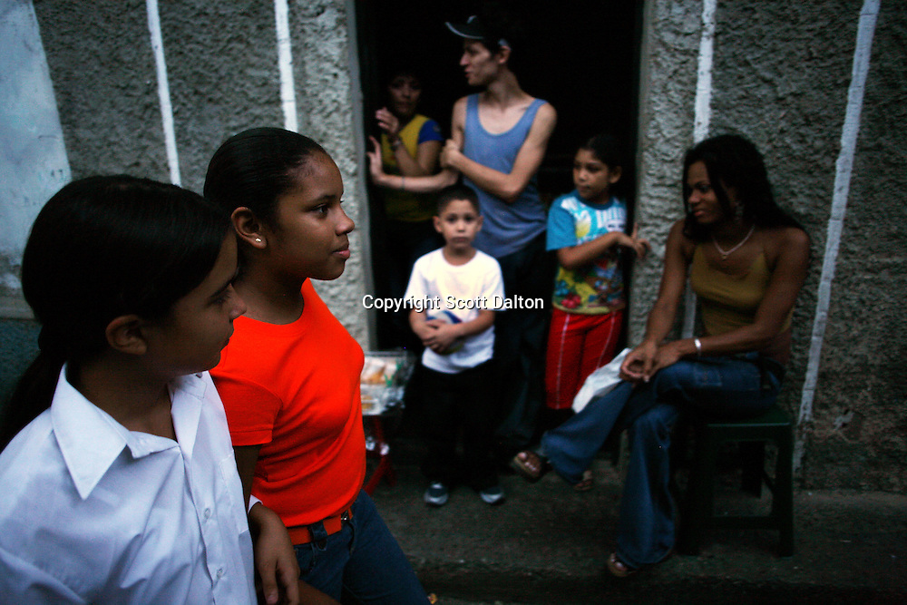 Stephany Rodriguez and Maira Rivero walk home together after attending the Don Bosco Center, a music center in the poor barrio of Chapellin, in Caracas on November 9, 2006. The Venezuelan government sponsors the National System of Youth and Children's Orchestras of Venezuela, which provides instruments and music training to the countries youths. The program was founded 31 years ago and has over 250,000 children participating throughout the country. (Photo/Scott Dalton)