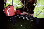 Cardiff University Ball in Cooper's Field, Cardiff, Wales, May 2000. Photograph © Rob Watkins. Pictured: St John's Ambulance take away a girl who has collapsed in the main marquee