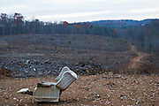 A beat-up reclining chair sits along in the barren, stripped remains of a forest.