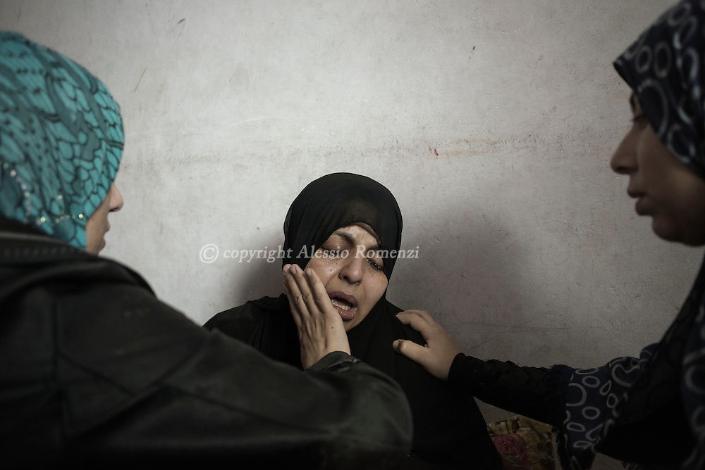 Gaza Strip, Gaza City: Relatives give confort to Suhar Elasem as his waiting the funeral of her two sons of seven and four years old killed by Israeli tank shell as they were in their house in the northern part of Gaza City. ALESSIO ROMENZI