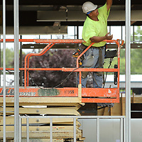Abel Macias, a framer with Klinkhammer, out of Dyersburg Tennessee, sets a window header in place as he helps his crew frame and prep for drywall on the student services building being constructed at the ICC Tupelo campus Tuesday afternoon.