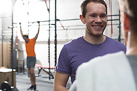 Happy man talking to male friend in crossfit gym