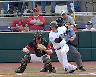 Kansas State's Joe Roundy (R) hits the ball down the first base line against Nebraska's Tony Watson.  Nebraska held on to be Kansas State 5-4 at Tointon Stadium in Manhattan, Kansas, April 1, 2006.