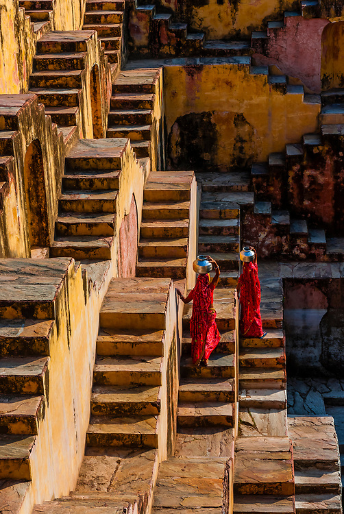 Two local women going to fetch water in Panna Meena Ka Kund step well, (baori), Amer (near Jaipur), Rajasthan, India.