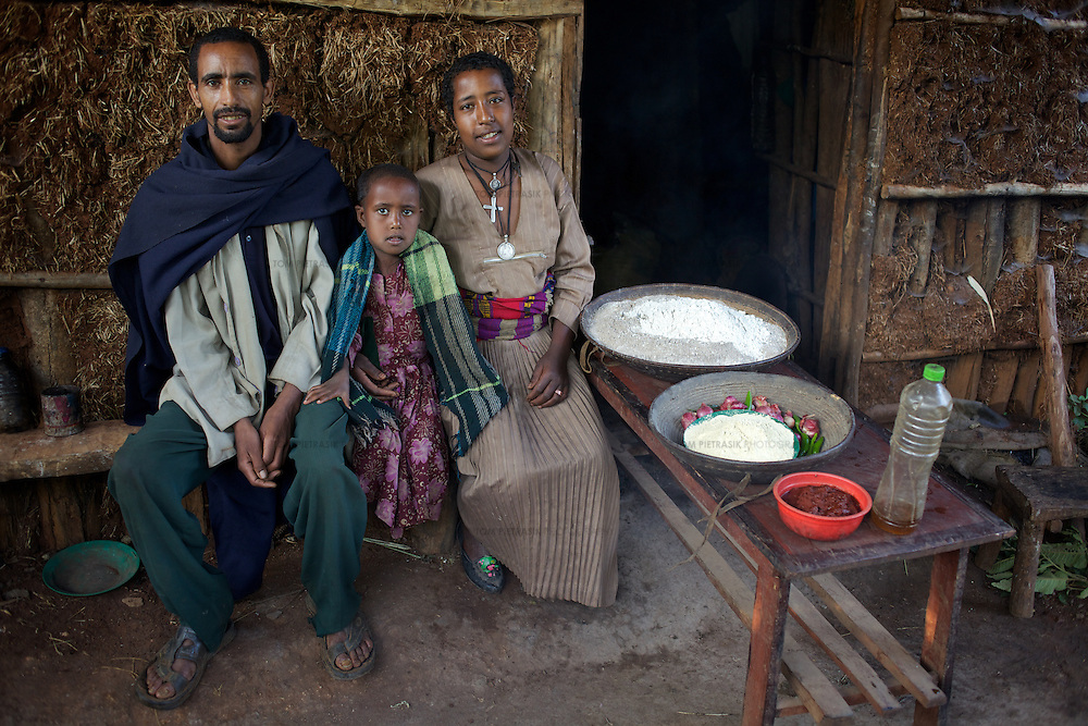 Wubalem, her husband Tsega and daughter Rekebki with a weeks supply of food outside their home. The food includes vegetables, maize and sorghum flours, vegetable oil and a paste of spices. <br /> <br /> Wubalem Shiferaw, age 23, lives in the village of Mecha with her husband Tsega Bekele, age 33, and their daughter Rekebki, age 4. Wubalem remembers her grandparents harvesting honey. She has maintained this tradition while moving to modern hives which produce a far greater yield of honey. Wubalem is a member of the Mecha village Cooperative which brings together local women beekeepers allowing them to share insights and build a credit union. The Mecha village Cooperative is not yet a member of the Zembaba Union. Wubalem's husband Tsega is a priest and a tailor. <br /> <br /> Harvesting honey supplements the income of small farmers in the Ethiopian region of Amhara where there is a long tradition of honey production. However, without the resources to properly invest in production and the continued use of of traditional, low-yielding hives, farmers have not been able to reap proper reward for their labour. <br /> <br /> The formation of the Zembaba Bee Products Development and Marketing Cooperative Union is an attempt to realize the potential of honey production in Amhara and ensure that the benefits reach small producers. <br /> <br /> By providing modern, high-yield hives, protective equipment and training to beekeepers, the Cooperative Union helps increase production and secure a steady supply of honey for which there is growing demand both in and beyond Ethiopia. The collective processing, marketing and distribution of Zembaba's &quot;Amar&quot; honey means that profits stay within the cooperative network of 3,500 beekeepers rather than being passed onto brokers and agents. The Union has signed an agreement with the multinational Ambrosia group to supply honey to the export market. <br /> <br /> Zembaba Bee Products Development and Marketing Cooperative Union also provides credit to individual members and trains carpenters in the pro