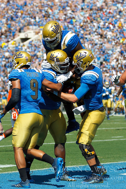 PASADENA, CA - SEPTEMBER 05:  Defensive lineman Kenny Clark #97 of the UCLA Bruins is congratulated by teammates after scoring a touchdown against the Virginia Cavaliers during the third quarter at the Rose Bowl on September 5, 2015 in Pasadena, California. The UCLA Bruins defeated the Virginia Cavaliers 34-16. (Photo by Jason O. Watson/Getty Images) *** Local Caption *** Kenny Clark