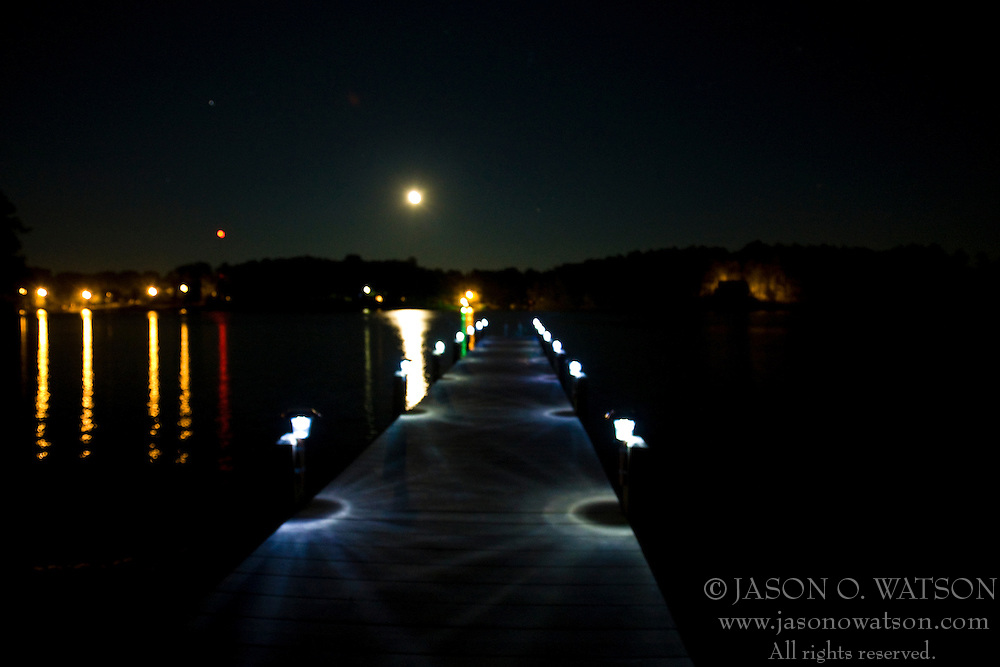 A rising full moon shines over Lake Greenwood and an illuminated dock over the water.