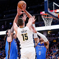 09 November 2017: Denver Nuggets center Nikola Jokic (15) takes a jump shot over Oklahoma City Thunder guard Russell Westbrook (0) and Oklahoma City Thunder center Steven Adams (12) during the Denver Nuggets 102-94 victory over the Oklahoma City Thunder, at the Pepsi Center, Denver, Colorado, USA.