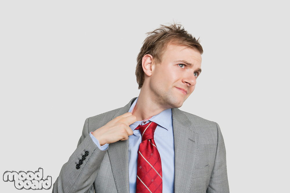Tired young businessman loosening tie over colored background