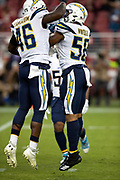 Los Angeles Chargers rookie linebacker Uchenna Nwosu (58) celebrates with Los Angeles Chargers defensive end Chris Landrum (46) after sacking San Francisco 49ers quarterback C.J. Beathard (3) for a first quarter loss of 7 yards during the 2018 NFL preseason week 4 football game against the San Francisco 49ers on Thursday, Aug. 30, 2018 in Santa Clara, Calif. The Chargers won the game 23-21. (©Paul Anthony Spinelli)