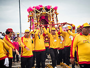 "23 JUNE 2015 - MAHACHAI, SAMUT SAKHON, THAILAND: Men carry the City Pillar Shrine to the Tha Chin (Chin River) during the procession for the shrine in Mahachai. The Chaopho Lak Mueang Procession (City Pillar Shrine Procession) is a religious festival that takes place in June in front of city hall in Mahachai. The ""Chaopho Lak Mueang"" is  placed on a fishing boat and taken across the Tha Chin River from Talat Maha Chai to Tha Chalom in the area of Wat Suwannaram and then paraded through the community before returning to the temple in Mahachai.   PHOTO BY JACK KURTZ"