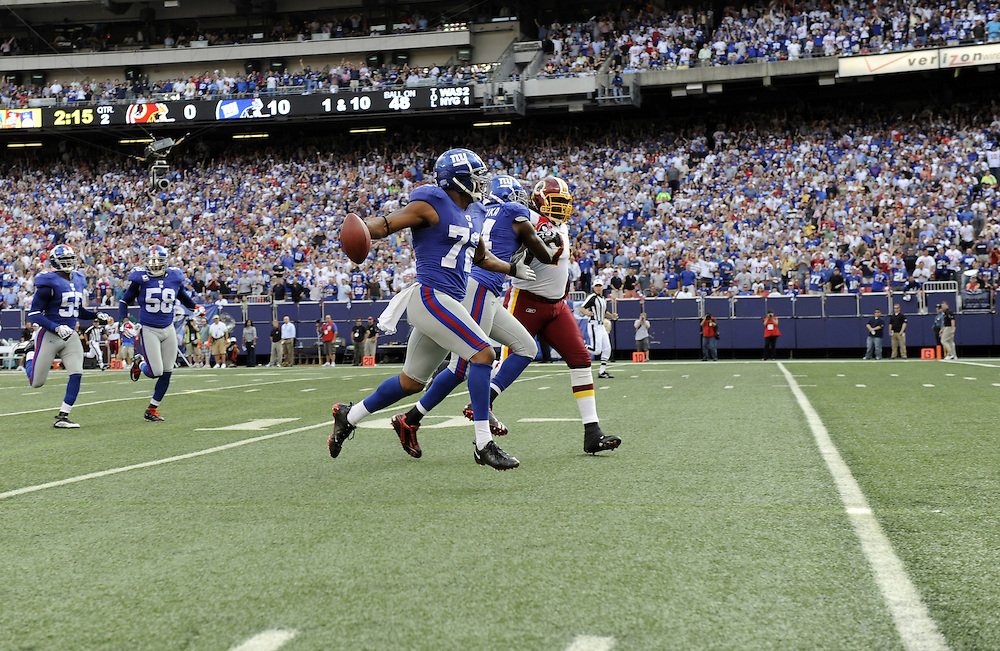 EAST RUTHERFORD, NJ - SEPTEMBER 13: Osi Umenyiora #72 of the New York Giants runs with the ball towards the goal line after recovering a fumble against the Washington Redskins during their game on September 13, 2009 at Giants Stadium in East Rutherford, New Jersey. (Photo by Rob Tringali) *** Local Caption *** Osi Umenyiora