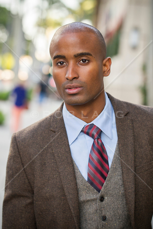 African American man in a suit standing on the street