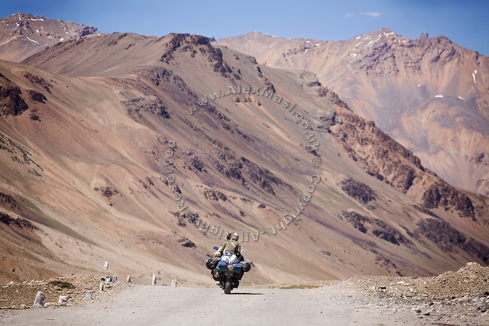 Two adventurous tourists on bikes are riding along the Leh-Manali Highway...The Leh-Manali Highway is the main road connection between the remote mountainous region of Ladhak, with capital in Leh (3300m), and Manali, HP, a famous hill station 600 km north of New Delhi. Open only four months a year, it is the second-highest motorable road in the world crossing passes up to 5300 meters. It was constructed by the Indian Army in order to develop the surrounding areas as well as monitoring the nearby borders with Kashmir and China. Due to its beauty and increased accessibility, the road to Leh and Ladhak has recently become a must-see destination for local and international tourists leaving the scorching Indian plains..