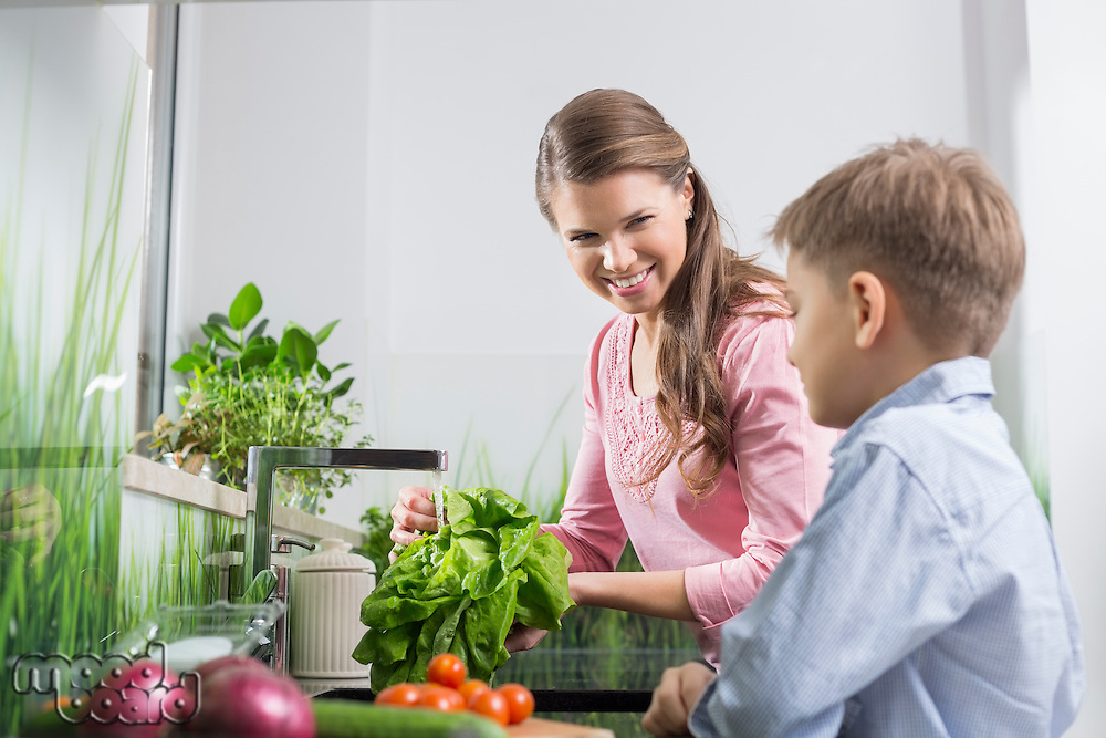 Happy mother and son washing vegetables in kitchen