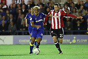 AFC Wimbledon striker Lyle Taylor (33) battles for possession with Brentford defender Henrik Dalsgaard (22) during the EFL Cup match between AFC Wimbledon and Brentford at the Cherry Red Records Stadium, Kingston, England on 8 August 2017. Photo by Matthew Redman.