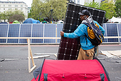 London, UK. 23rd April 2019. A climate change activist from Extinction Rebellion removes solar panels from the camp at Marble Arch following a Metropolitan Police operation to surround the stage.