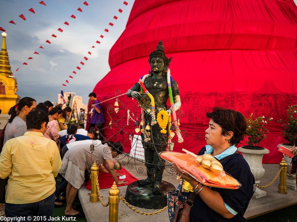 20 NOVEMBER 2015 - BANGKOK, THAILAND: People pray as the walk around the chedi at the top of Wat Saket during the annual temple fair. Wat Saket is on a man-made hill in the historic section of Bangkok. The temple has golden spire that is 260 feet high which was the highest point in Bangkok for more than 100 years. The temple construction began in the 1800s in the reign of King Rama III and was completed in the reign of King Rama IV. The annual temple fair is held on the 12th lunar month, for nine days around the November full moon. During the fair a red cloth (reminiscent of a monk's robe) is placed around the Golden Mount while the temple grounds hosts Thai traditional theatre, food stalls and traditional shows.     PHOTO BY JACK KURTZ