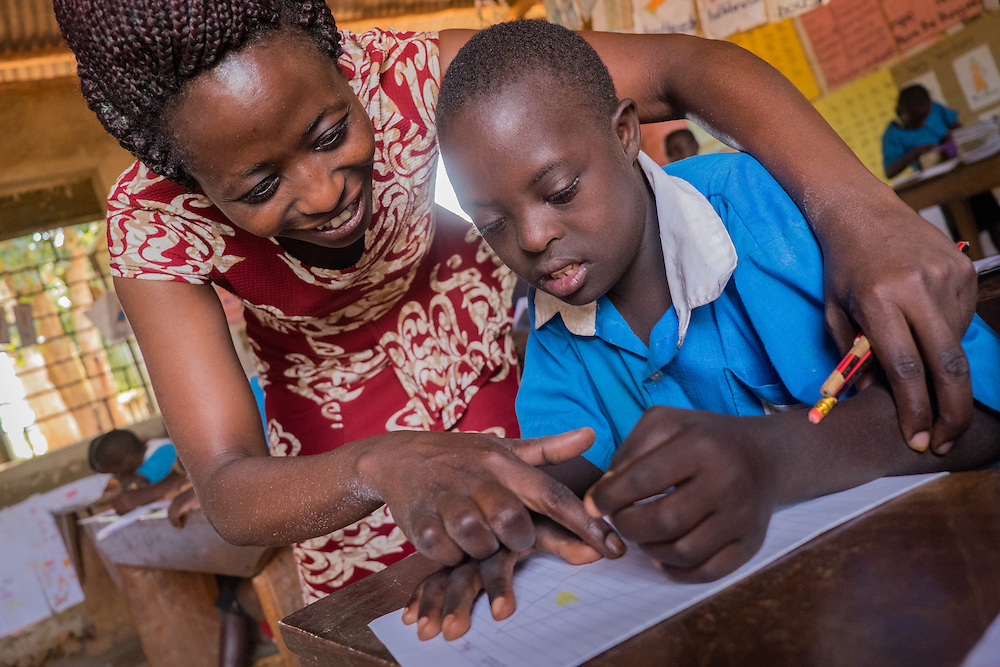 CAPTION: Teacher Margaret Nabwami uses tactile methods to help Junior, a student with both a hearing impairment and a learning disability, during class. Ms Nabwami is a SignHealth Uganda 'focus teacher' at Butenga-Kibanda Primary School. She has received special training in how to work with children who have hearing impairments, which she puts into effect in her own classroom and also teaches to other staff at the school. LOCATION: Butenga-Kibanda Primary School, Butenga Village, near Masaka City, Bukomansimbi District, Central Region, Uganda. INDIVIDUAL(S) PHOTOGRAPHED: Left: Margaret Nabwami; right: Junior Steven Ssengodze.