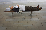 Guarding his walking stick, an elderly gentleman sleeps on a city street bench in central London.