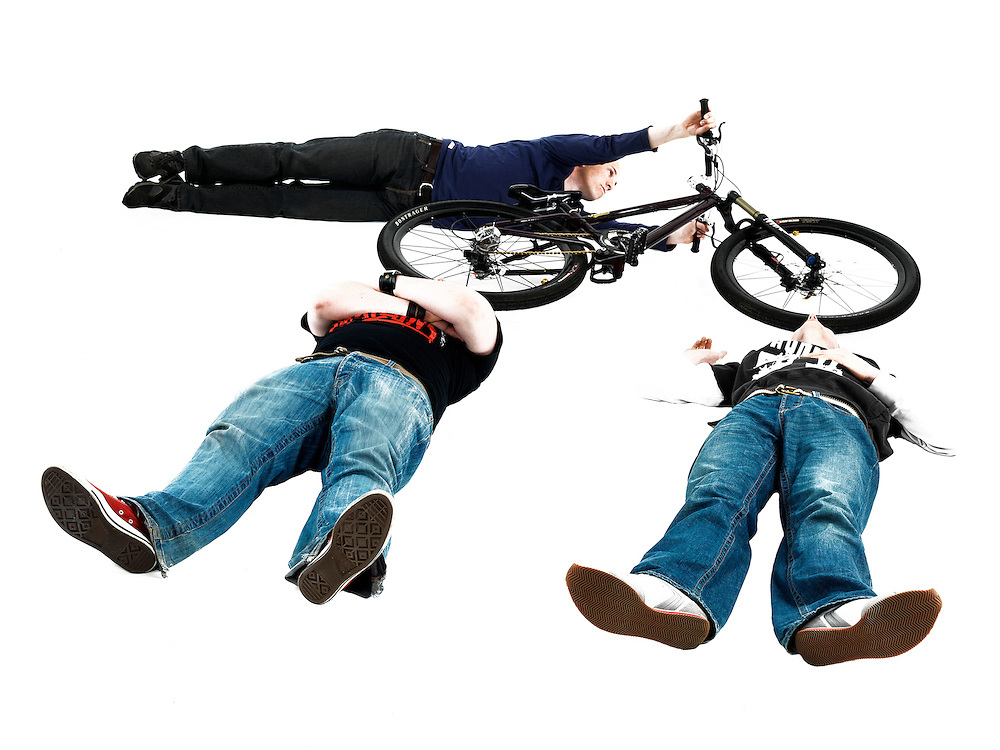 Mountain Biker Jumping Over Two Men on White Background